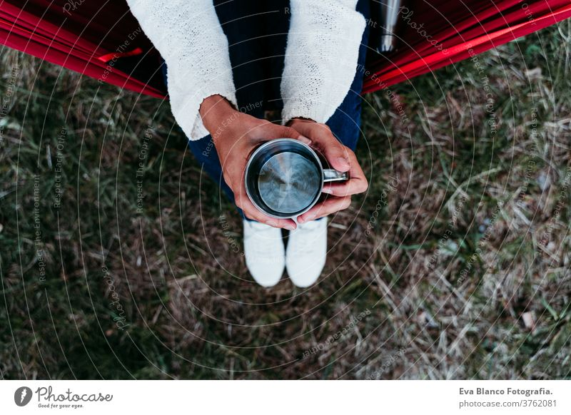 top view of woman holding metallic mug of water, relaxing in hammock at sunset. autumn season thermos unrecognizable feet lying outdoors nature orange park