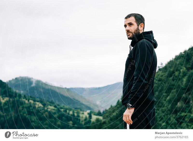 Young male nature explorer enjoying the view on op of the mountain adult adventure alone bearded casual caucasian cloudy countryside dawn environment freedom