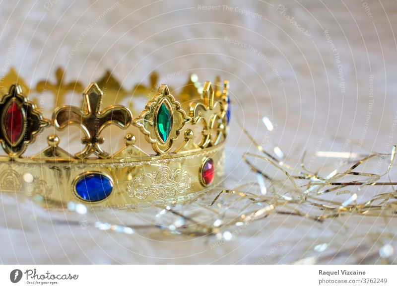Royal gold crown, with colored gems and diamonds, on a white background with golden bands surrounding it. christmas decoration holiday jewelry royalty king