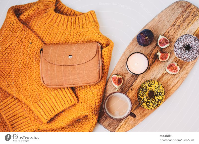 cozy autumn morning flat lay composition with warm sweater, cup of coffee, sweet donut for breakfast and fashion handbag fall winter decoration drink knitted