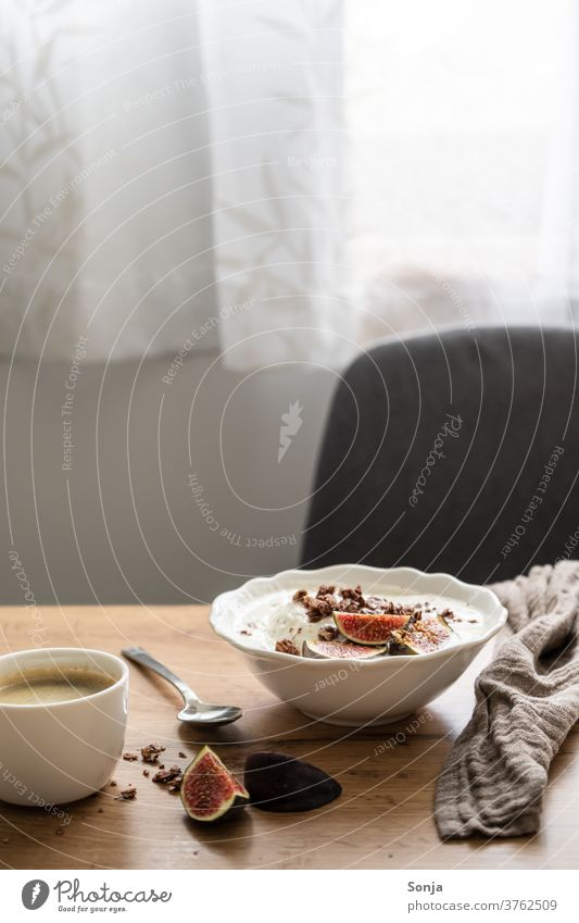 Set breakfast table with granola, yoghurt and fresh figs and a cup of coffee. Window light, morning sun. Breakfast table Yoghurt Fig Coffee Cup bowls Table