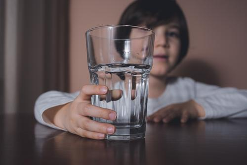 Child with water glass beverage big boy caucasian child childhood clean closeup cute daily diet drink eyes face finger fresh hand health healthy hold home