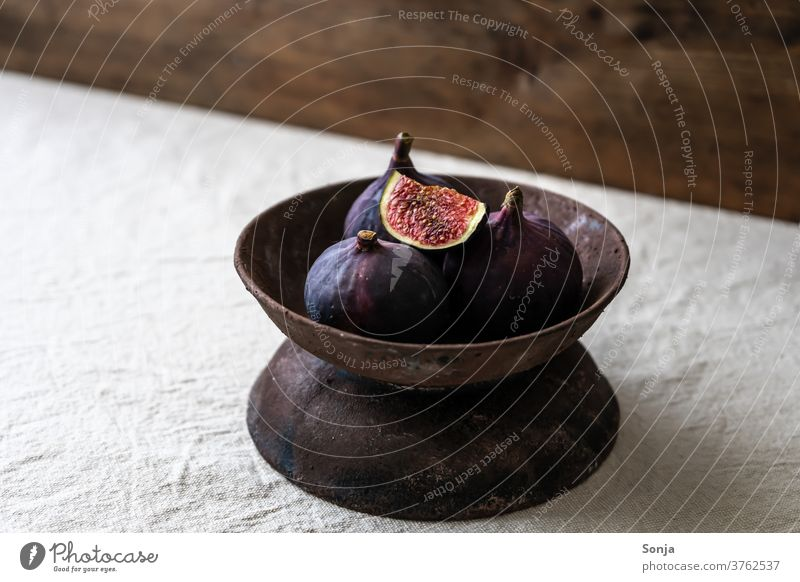 Fresh figs in a rustic bowl on a beige linen tablecloth. Fig bowl fruit bowl Rustic Raw Healthy Mature Organic natural Diet Table wood Nutrition Ingredients