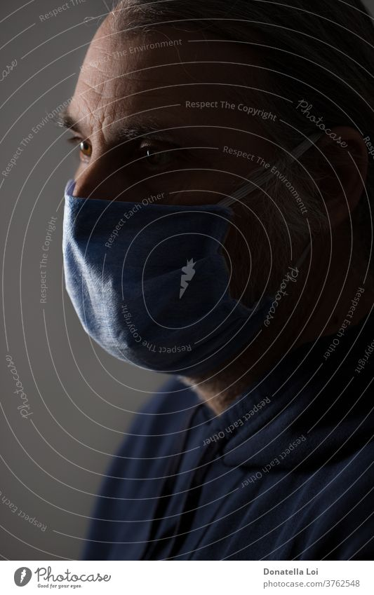 Portrait of Middle-aged man with protective mask bacteria close up common cold concept contagious coronavirus covid-19 disease epidemic face fever flu hand head