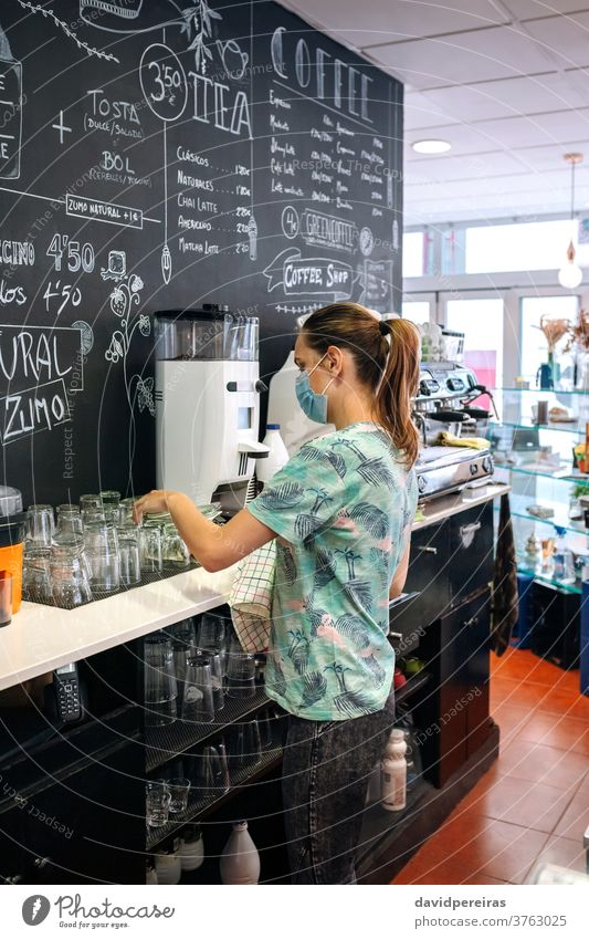 Waitress with mask cleaning glasses waitress placing dish towel face mask coronavirus written blackboard coffee maker coffee machine reviewing coffee shop
