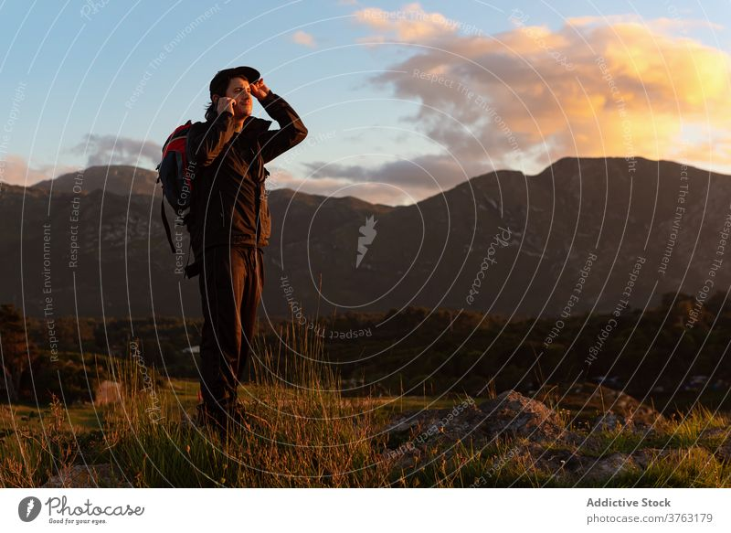 Male hiker with backpack in highland valley traveler hill man mountain admire explore sunset sky vacation sundown ridge landscape scenic rock majestic guy