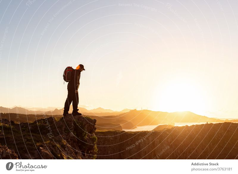 Unrecognizable traveling man on hill at sunset hiker backpack mountain admire vacation sundown trekking male rock amazing relax chill adventure scenic landscape