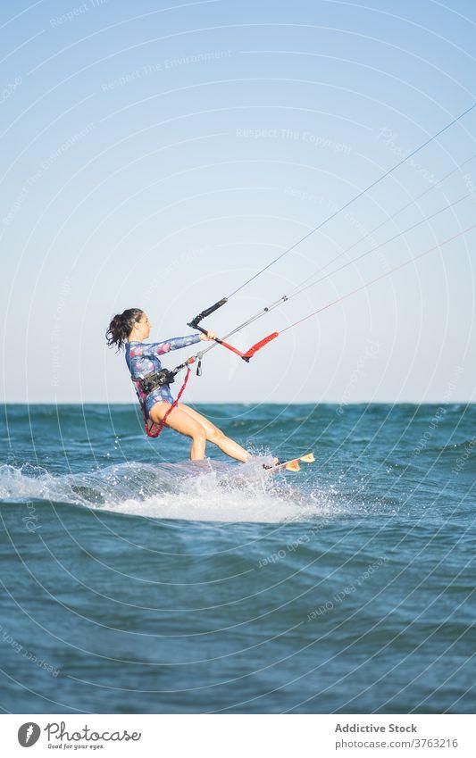 Female kite surfer riding on board in sea woman ride wave splash summer professional female swimsuit fit ocean recreation holiday swimwear surfing surfboard