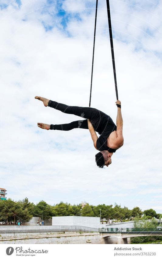Flexible man training on aerial straps gymnast gymnastic hang perform flexible fit park male workout exercise energy athlete sport healthy sportswear effort