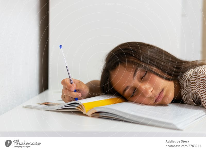 Tired student sleeping at table tired woman exhausted prepare exam textbook overwork female education study young knowledge asleep fatigue homework research