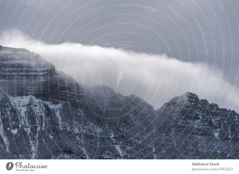 Snowy mountain ridge in winter range snow cloudy sky fog dramatic highland landscape amazing pyrenees huesca spain scenery spectacular cold nature environment