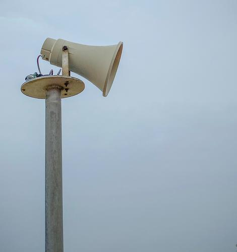 Side view of an older loudspeaker in the shape of a megaphone in front of a bluish hazy sky Loudspeaker Megaphone Pole Sky announcement Communicate Information