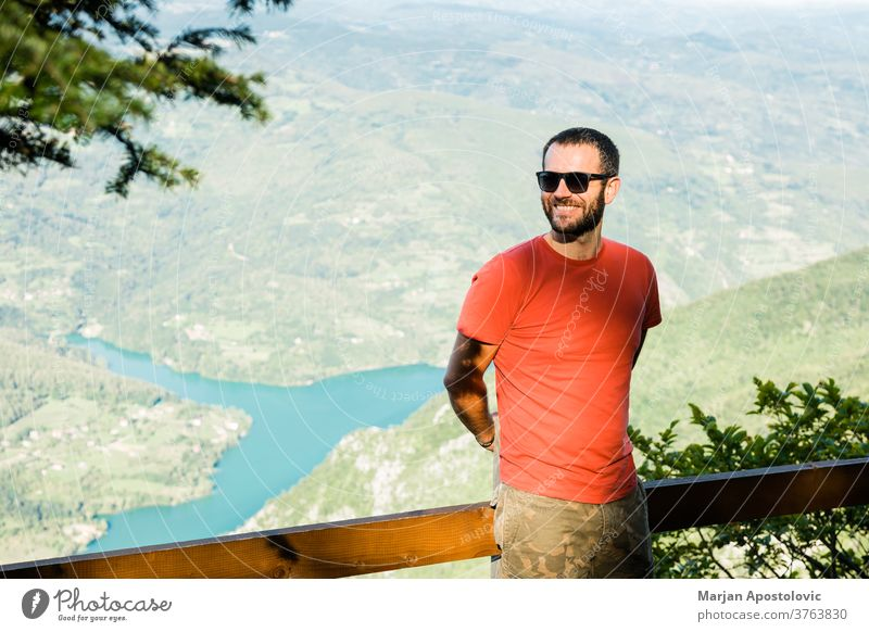 Young man in the mountain enjoying the view of the lake adventure alone background beautiful canyon caucasian day edge explore explorer free freedom guy