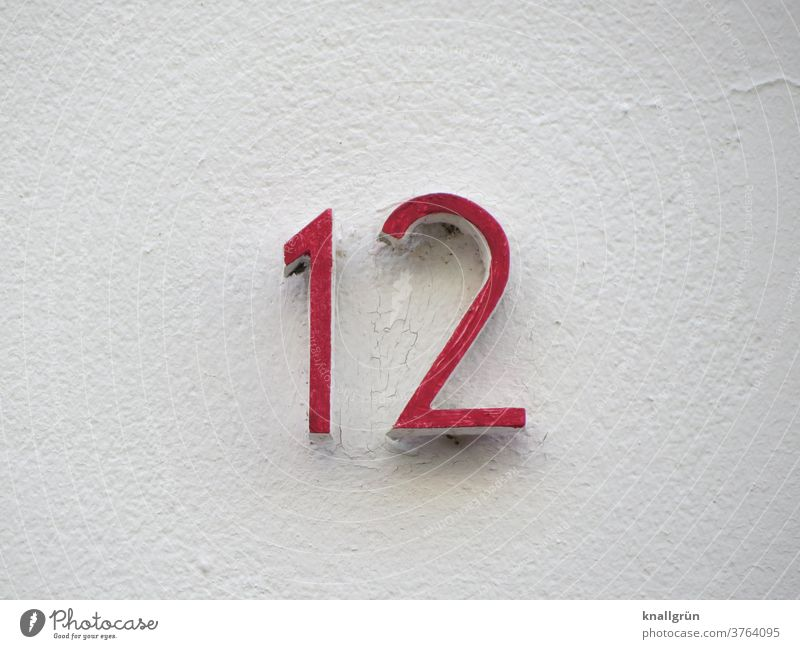 Red house number 12 on a white house wall House number Digits and numbers Wall (building) Facade Signs and labeling Wall (barrier) Exterior shot Colour photo