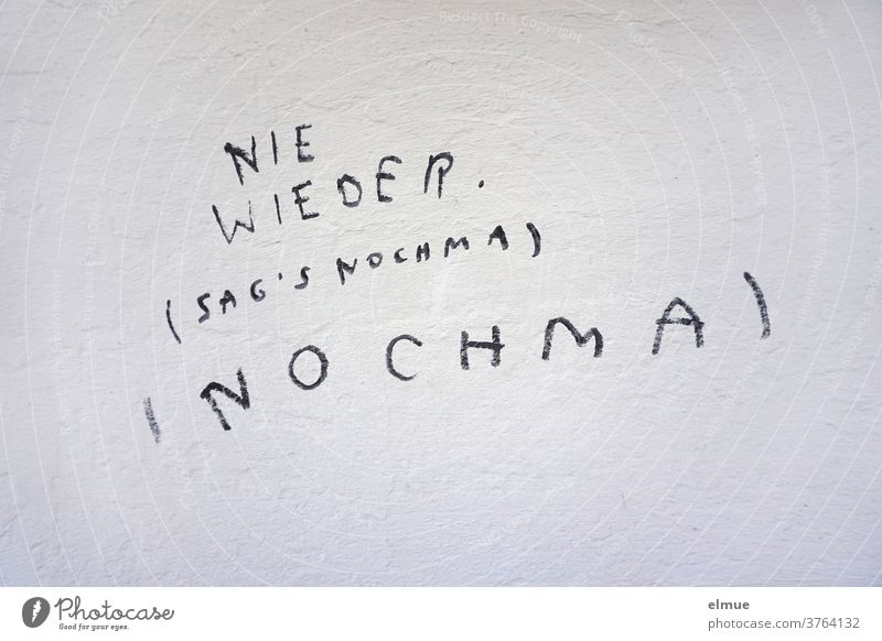 """NEVER Say NOCHMA"" is written in block letters in black on the gray wall never again Daub Repeating quibbling Say it again opinion formation reenact Spelling"