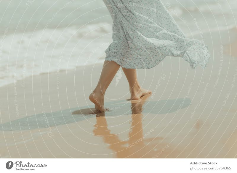 Anonymous woman in dress walking on sandy beach barefoot leg shore coast alone pure sea gentle female spain valencia el saler beach nature romantic freedom