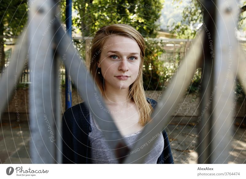 Close portrait of a young woman standing behind a sliding gate and looking through it Woman Young woman Slim already athletic Blonde youthful 18-25 years