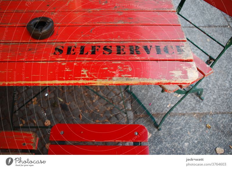Self-service labelled on wooden table Table Folding chair English Typography Stencil letters Word Ravages of time Capital letter Second-hand Ashtray Clue wear
