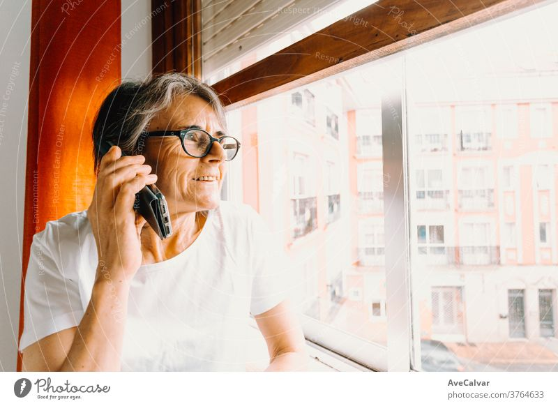 Close up of an old woman making a call on the mobile phone and smiling while looking through the window grandmother indoor retirement person communication