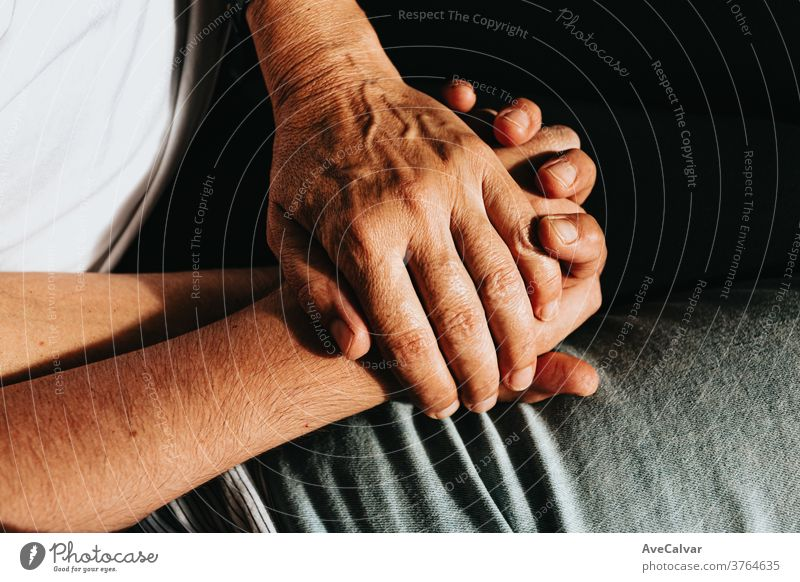Close up of two old hands grabbing a young hand on cinematic tones assistance community females friendship grandparent holding hands horizontal reaching