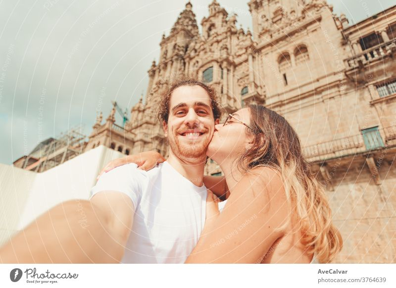 Young man taking a selfie and smiling while his girlfriend kisses him adult feeling white fun portrait pose woman hugging boyfriend young couple hold happiness