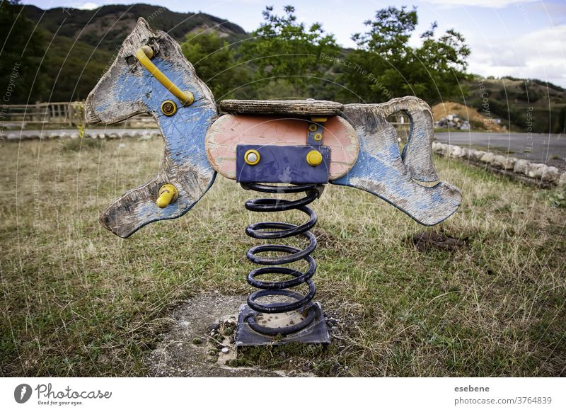 Abandoned rocking horse in playground white antique lonely isolated ride joy attraction wooden spring kindergarten seesaw broken aged chair cute weathered