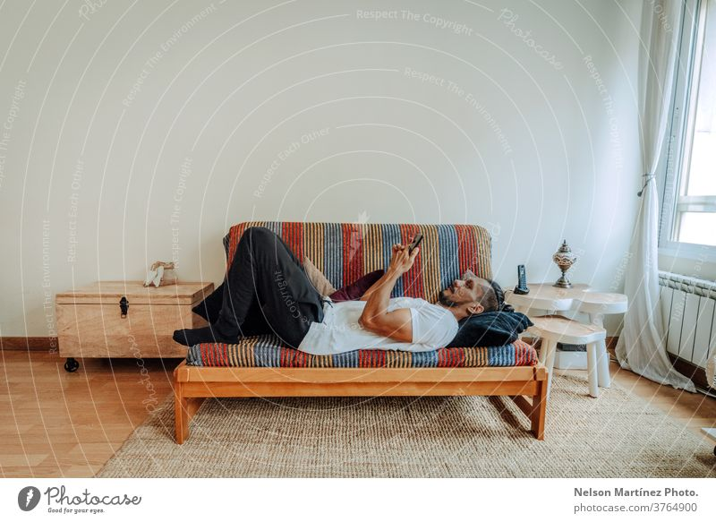 Hispanic man lying on a colourful coach relaxed. He is using a smartphone. mobile indoor home mobile phone person people morning 1 working call communication