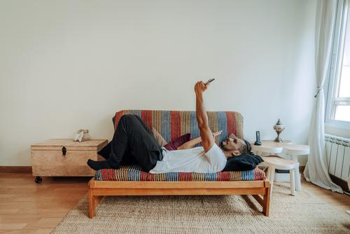 Hispanic man lying on a colourful couch relaxed. He is texting and using a smartphone. mobile indoor home mobile phone person people morning 1 working call