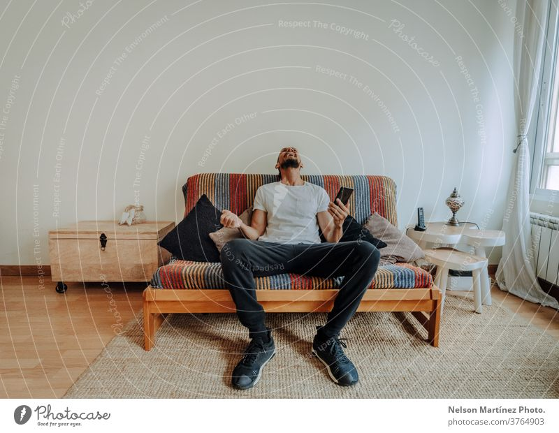 Hispanic man siting on the couch. He is laughing with his smartphone in his hand. 1 freedom adult looking casual attire lifestyle holiday vacation latin alone