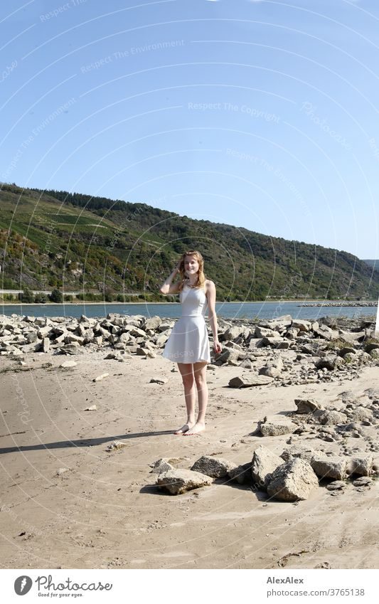 Backlit portrait of a young, barefoot woman on the banks of the Rhine Woman Young woman Slim already athletic Blonde youthful 18-25 years red blonde hair look