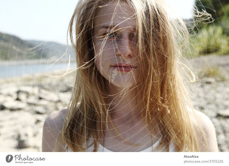 Close up backlight portrait of a young, freckled woman with wind-blown hair on the banks of the Rhine Woman Young woman Slim already athletic Blonde youthful