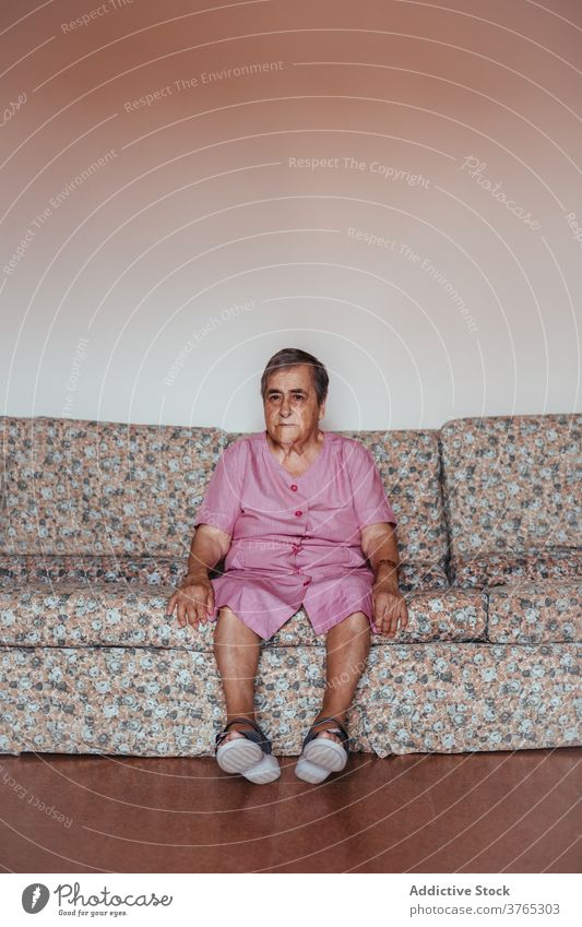 Senior woman sitting alone on the sofa at home old loneliness indoors alzheimer mental health one person retirement memory aged home interior grandmother senior