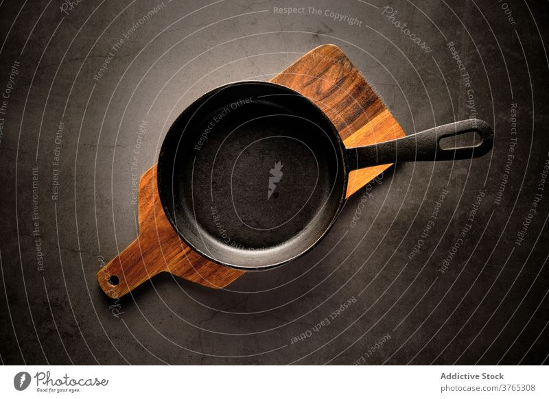 Empty frying pan on table kitchen cookware culinary prepare household cutting board wooden cuisine tableware appliance chopping board domestic lumber dishware