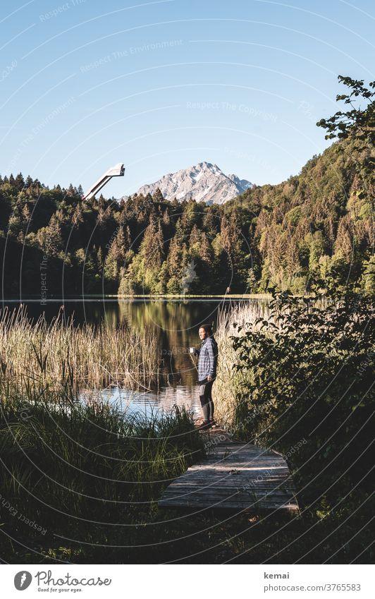 Person drinks coffee at the lake against a mountain backdrop allgau Oberstdorf Peak Lake ski jump Forest Water Footbridge Woman teen Coffee Coffee cup Camper