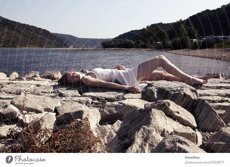 Backlit portrait of a young, barefoot woman on the banks of the Rhine, lying on a dam Woman Young woman Slim already athletic Blonde youthful 18-25 years