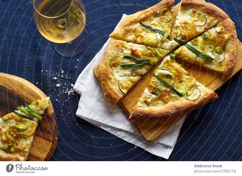 Top view of vegetarian pizza zucchini onion blue orange wine cheese crust salt italian cuisine food meal flatlay top view overhead zucchini flowers rustic
