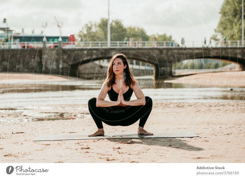 Slim woman in Garland pose doing yoga on beach garland pose malasana practice balance summer female shore mat tranquil river healthy slim harmony peaceful