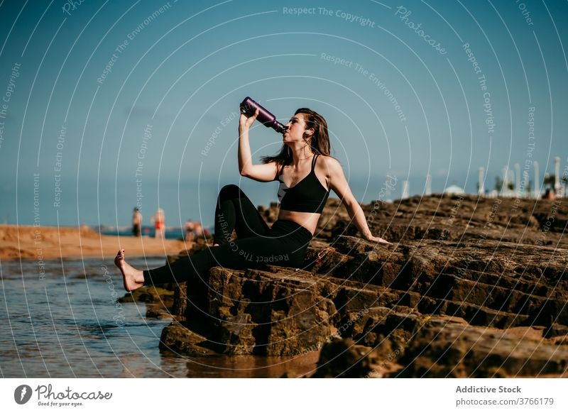 Tranquil woman sitting drinking water after yoga shore padmasana zen female stress relief stone sportswear wellness tranquil peaceful harmony practice relax