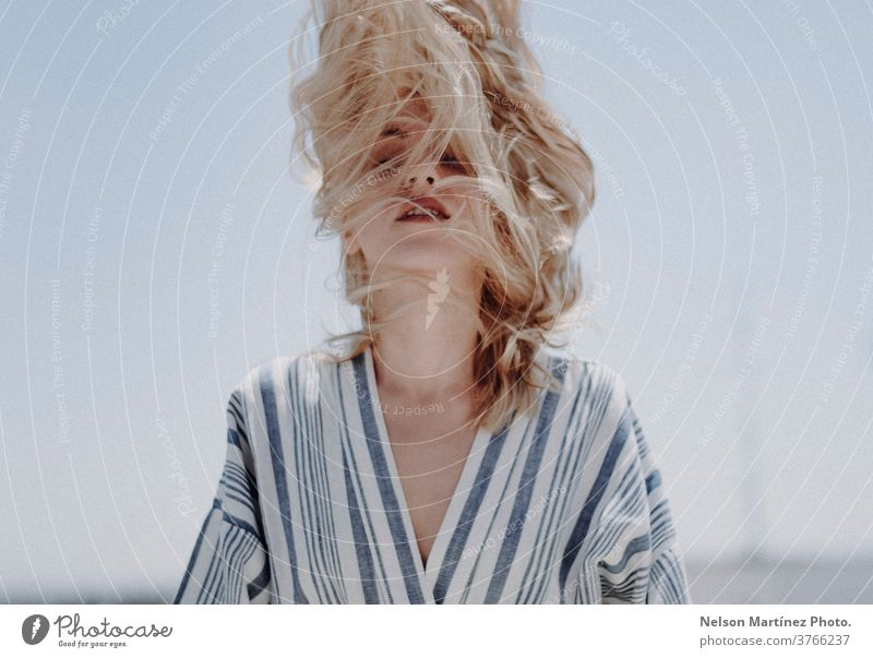 Portrait of a caucasian blonde woman.  She is shaking her head with the hairs covering her face. shake fashion lifestile conceptual Caucasian