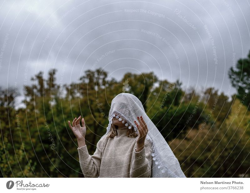 Portrait of a caucasian blonde woman wrapped with a white tulle on her head. portrait tullle creative concept design young art creativity background artistic