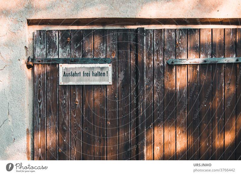 there should be no parking in front of the old garage door Garage Goal Garage door Old vintage Double doors sign Highway ramp (entrance) Day Highway ramp (exit)