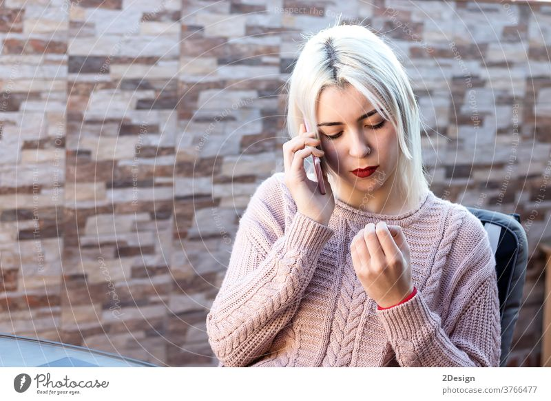 Happy blonde young woman sitting outdoors while talking with cellphone mobile person adult female communication technology mobile phone lifestyle beautiful city