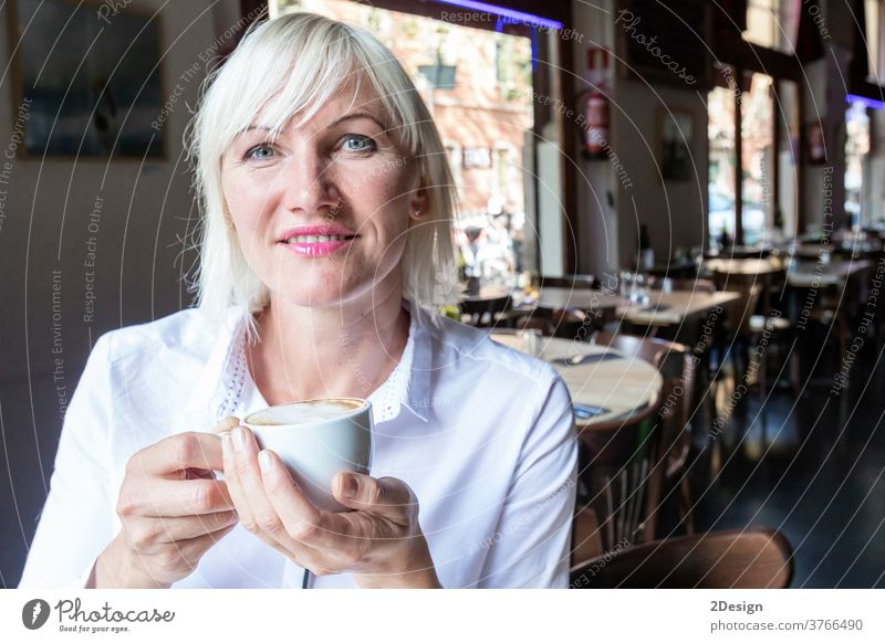 Young blonde woman drinking coffee in cafe person sitting cup female lifestyle table smiling business girl young indoor happy adult beautiful smile one person