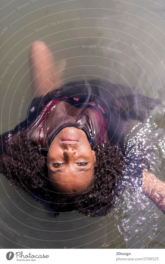 Beautiful young black woman into water while looking camera afro portrait mobile vacation summer beach travel people model sea fashion beautiful pensive