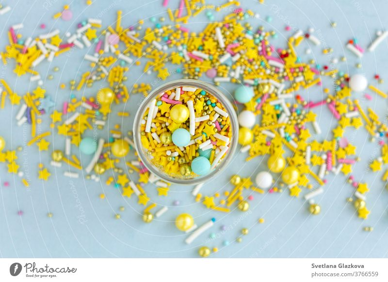 Yellow sugar sprinkles grainy on blue background, close-up flat lay colorful candy sweet food dessert birthday holiday pink cake confetti closeup yellow party