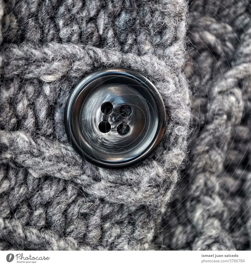 black button in gray wool, grey background thread fabric cloth textured abstract pattern material industry textile design handmade detail macro knitting