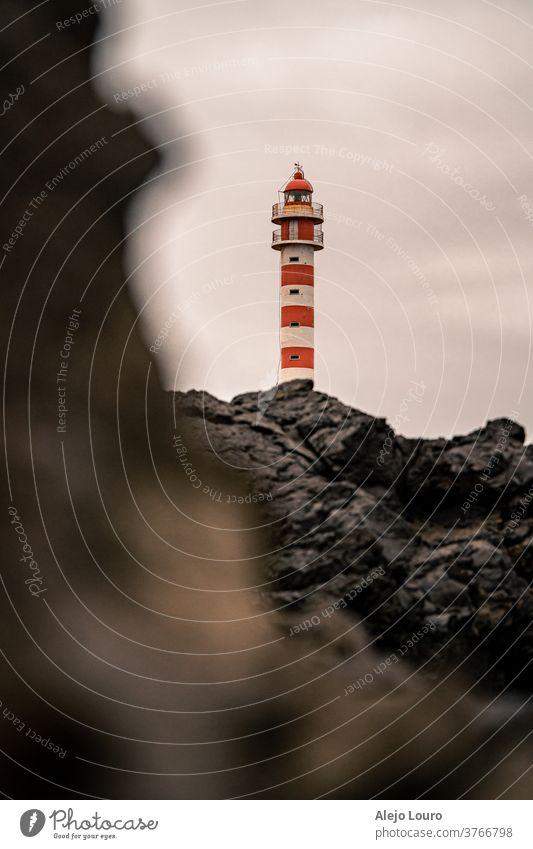 Red and white lighthouse seen behind vulcanic rocks on a grey day. beacon building canary coast coastline europe gran canaria island landmark landscape maritime