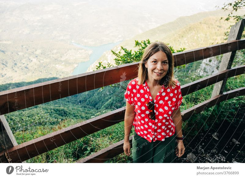 Young female nature explorer enjoying the view from mountain viewpoint lake adult adventure alone background beautiful casual caucasian destination environment