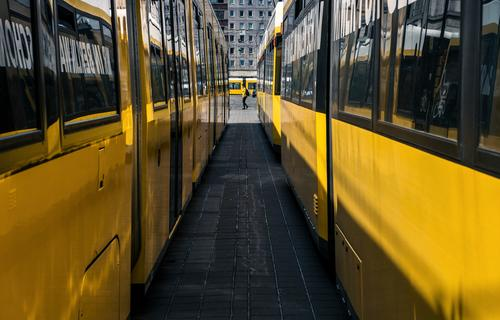 Trams from all sides and a suitably dressed woman Yellow Berlin Street Transport urban person Passer-by Perspective Tunnel vision Window Vanishing point