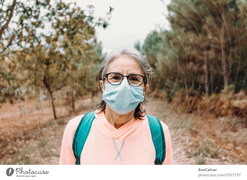 Close up of a frontal portrait of an old woman wearing a mask and sport clothes in the forest during a trekking day person elderly exercising fear horizontal